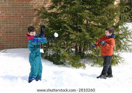 Two Boys having a snowball fight outside in the Snow - stock photo