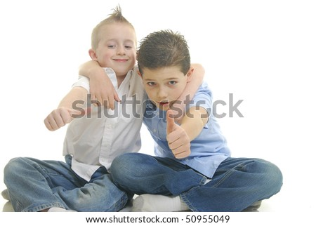 Two boys  hugging with thumbs up, isolated on white. - stock photo