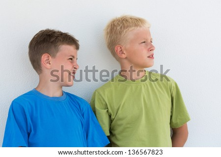 Two boys in colored T-shirts somewhere looking - stock photo