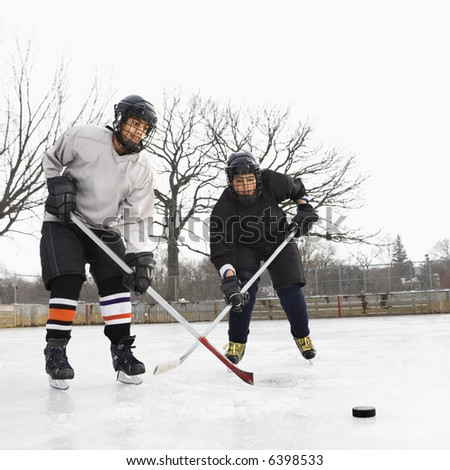 Two boys in ice hockey uniforms playing hockey on ice rink. - stock photo