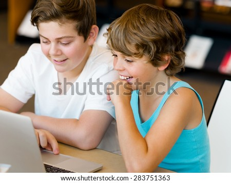 Two boys in library with notebook - stock photo