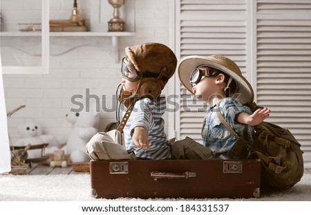 Two boys in the form of an aircraft pilot and traveler playing in her room - stock photo