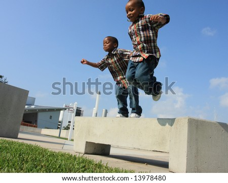 Two Boys Jumping from a Bench - stock photo