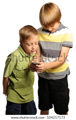 Two boys Looking at a portable internet device. Seven and nine year old boys looking at a portable internet device. - stock photo