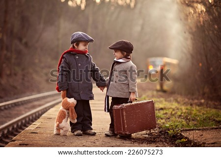 Two boys on a railway station, waiting for the train with suitcase and teddy bear - stock photo