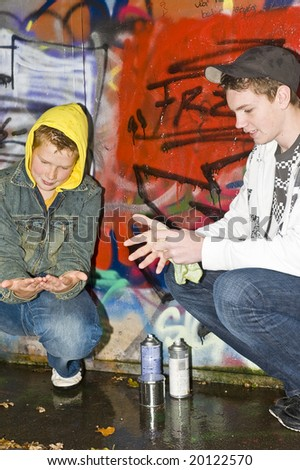 Two boys, outdoors, cleaning their hands from paint. - stock photo