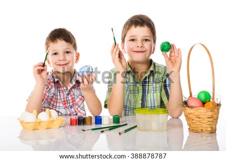 Two boys painting easter eggs, isolated on white - stock photo