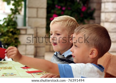 Two boys play a board game, one boy hold out a hand with a card - stock photo