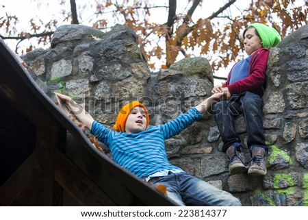 two boys playing outside on a playground - stock photo