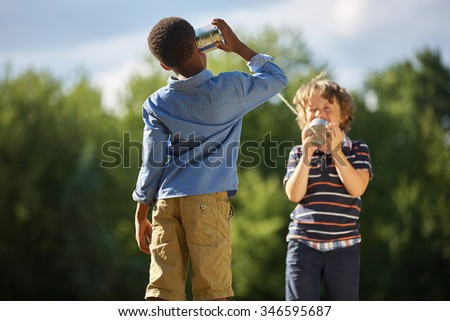 Two boys playing tin can telephone and having fun at the park - stock photo