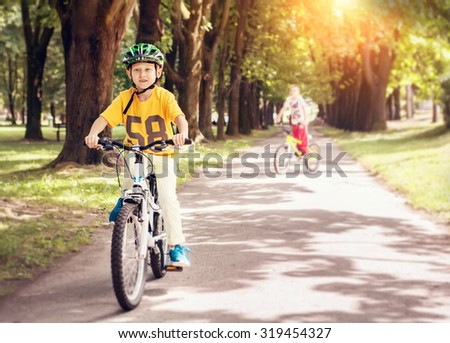 Two boys ride a bicycle in park - stock photo
