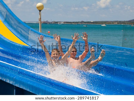 two boys ride at a water park with slides - stock photo