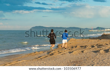 Two boys running on the sand at the beach - stock photo