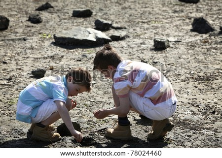 two boys searching for crabs at a beach - stock photo