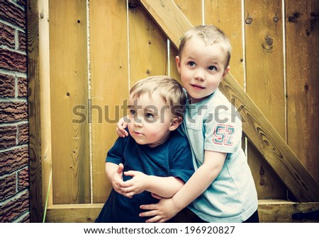 Two boys stand together hugging looking up.  Filtered in retro, faded, Instagram look.  - stock photo