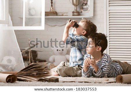 Two boys travelers studying maps and old books in his room - stock photo