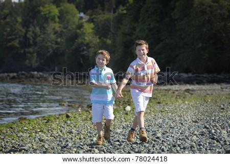 two boys walking on a beach - stock photo