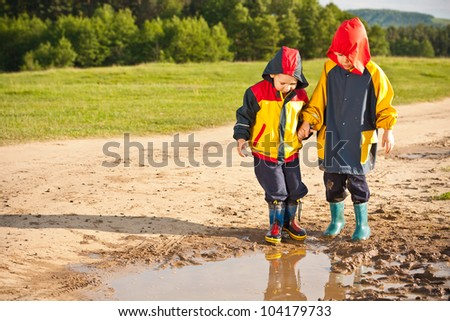 Two boys walking through a mud puddle in her rain coat and boots. - stock photo