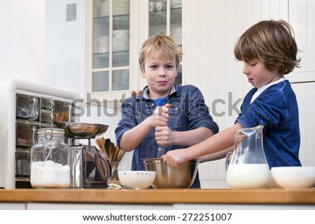 Two boys whisking dough for pastry in a stainless steel in a kitchen - stock photo