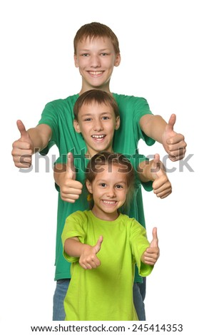 Two boys with little girl thumbs up on white - stock photo