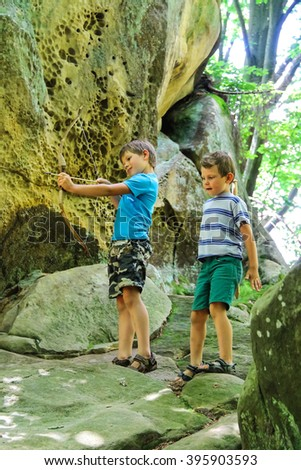 Two boys with wooden bow and a sword. - stock photo