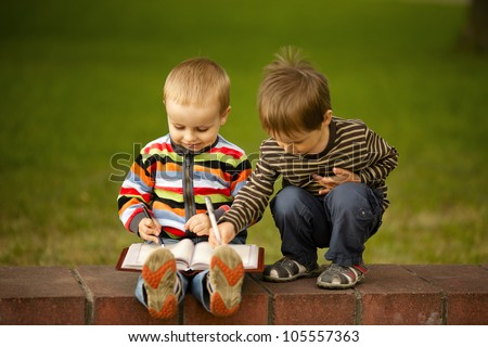 two boys write in a notebook - stock photo