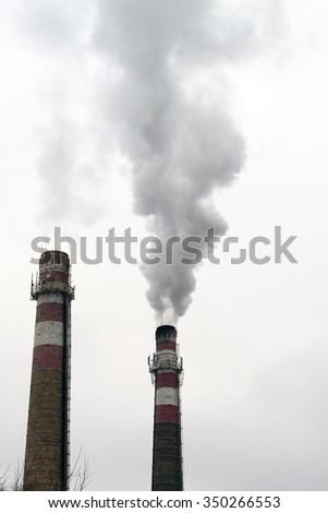 two brick smokestacks with black smoke - stock photo