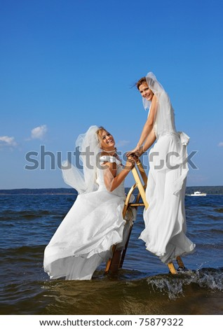 two brides on stepladder in sea waters - stock photo