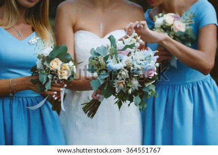 Two bridesmaids in blue dress and bride with luxury bouquets on the wedding ceremony outdoors. - stock photo