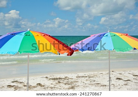 Two Bright Color Beach Umbrellas on the Beach - stock photo
