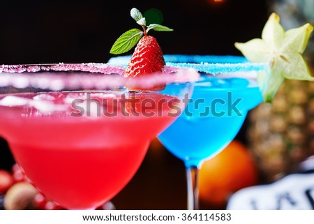 two bright refreshing cocktails: blue margarita and strawberry daiquiri. - stock photo