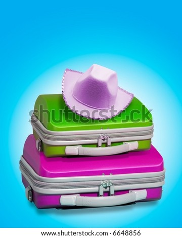 Two bright suitcases with a female cowboy party hat in pink resting on top. Displayed against a bright blue background with clipping path supplied - stock photo