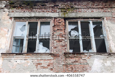 Two broken windows in an old abandoned building - stock photo