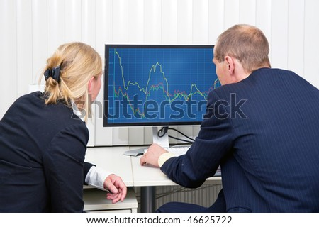 Two brokers analyzing (sales) trends, displayed on a flat screen monitor - stock photo
