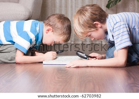 Two brothers are looking through a magnifying glass, indoor - stock photo