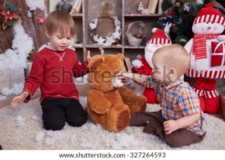 two brothers are playing under the Christmas tree - stock photo