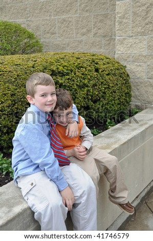 two brothers horsing around outside church - stock photo