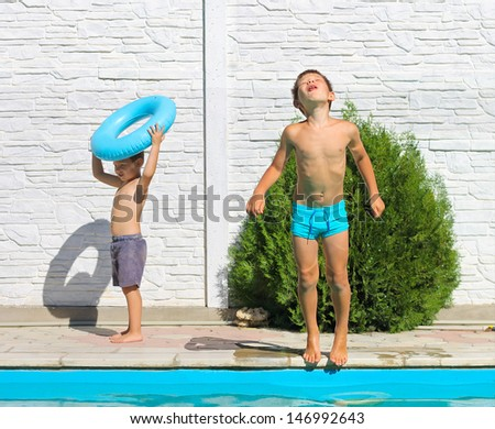 Two brothers near a swimming pool at summer vacation - stock photo