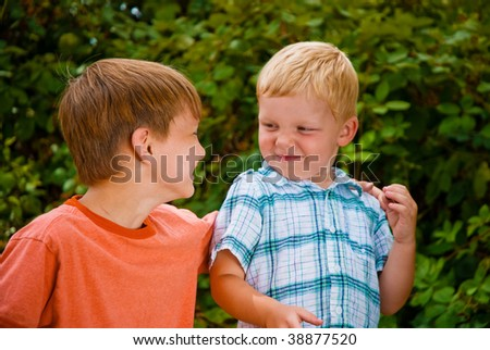 Two brothers playing at a blackberry farm - stock photo