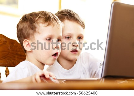 two brothers playing computer games indoor - stock photo