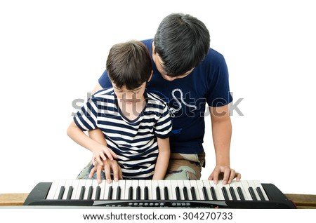 Two brothers playing keyboard piano together - stock photo