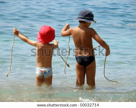 Two brothers playing on beach with rope - stock photo