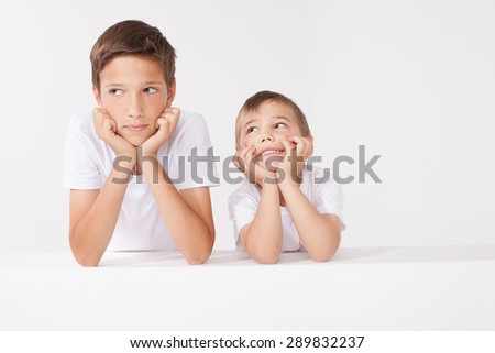 Two brothers posing in studio. Family portrait. - stock photo