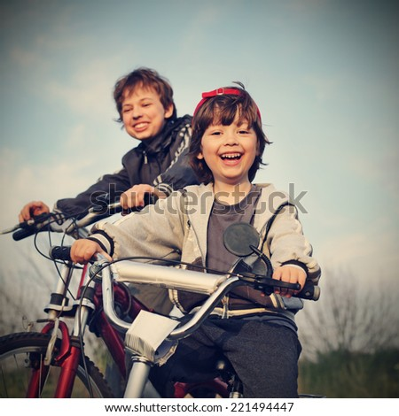 two brothers ride bikes - stock photo