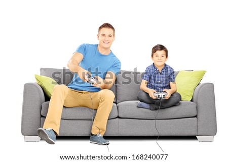 Two brothers seated on a sofa playing video games isolated on white background - stock photo