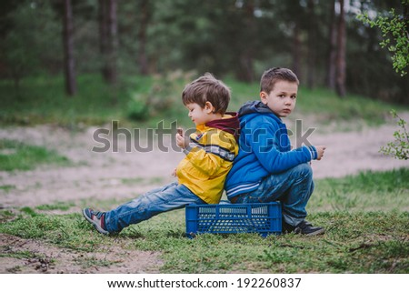 two brothers sitting in the forest eating. picnic - stock photo