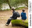 two brothers sitting on a mossy log by riverside - stock photo