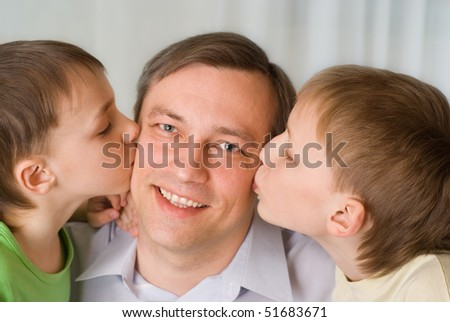 two brothers together kissing his lucky father - stock photo
