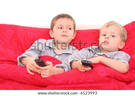 two brothers watching TV in bed - stock photo