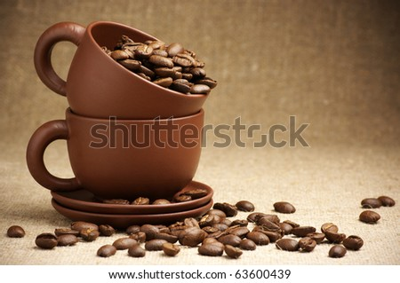Two brown ceramic cups with roasted coffee beans on canvas. - stock photo